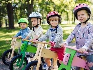 kinderen-met-houten-loopfietsen